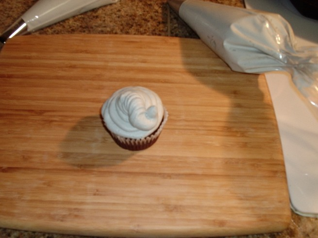 Beginning in the center, using even pressure, squeeze bag and move your hand slightly up and down and pulling toward your self and down, swirling up to the right when you reach the edge of the cupcake, creating the trunk